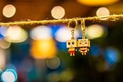 Two Man and Woman Wooden Couple Keychains Hanging on Rope Overlooking Bokeh Lights royalty free stock photos