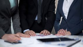 Two manager ladies and male boss comparing sales charts and investment plans. Stock photo stock photo