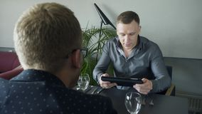 Two managers having morning business lunch meeting in restaurant. Brown-haired male speaking, explaining issues, holding tablet, diagram on screen. Blond man stock video footage