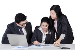 Two managers looking their partner signing document Stock Image