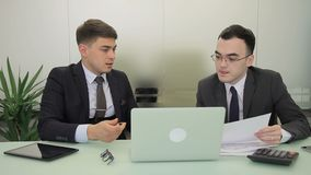 Two managers working, sitting at table with laptop in modern office. Young men talk actively, examine at documents and look attentively at screen of the stock video footage