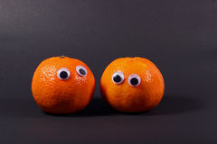 Two mandarin oranges with googly eyes Royalty Free Stock Photos