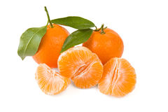 Two mandarines or tangerines with leaves and peeled one Royalty Free Stock Images