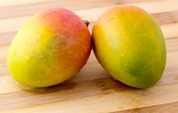 Two mango on carving board Stock Image
