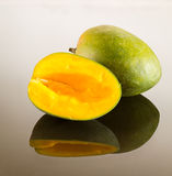 Two mangoes on reflecting surface Stock Photography