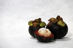 Two mangosteen and one peel on white background. stock photography