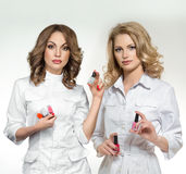 Two manicure masters holding nail polish Royalty Free Stock Image