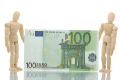 Two manikins holding euro bill. Two manikins holding hundred euro bill Royalty Free Stock Photography