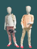 Two mannequins dressed in fashionable kids wear. Isolated on green background. No brand names or copyright objects Royalty Free Stock Photo