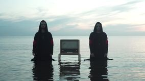 Two Mans With Radioreceiver In The Sea. Two mans with vintage radioreceiver in the calm sea in the summer evening stock video