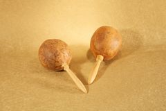 Two maracas on golden paper. Two maracas on golden textured paper at still life stock image