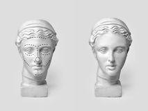 Two marble heads of young women, ancient Greek goddess bust marked with lines for plastic surgery and sculpture after Stock Images