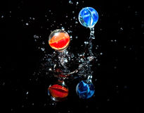 Two marbles bouncing on wet surface Stock Photos
