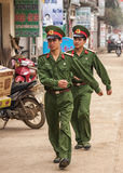 Two marching soldiers in the street of rural town. Royalty Free Stock Image