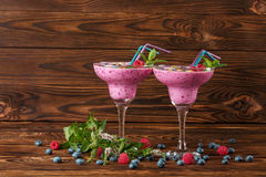 Two margarita glasses filled with colorful smoothie drinks on a wooden background. Refreshing beverages with juicy bright berries. Stock Photo