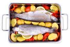 Two marinated trout with red pepper, potato, lemon Stock Photos