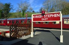 Platform sign and coaches kirkby stephen east station. Two Mark 1 Coaches BSK & TSO in maroon british railway livery and platform station sign at Stainmore royalty free stock photography