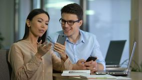 Two marketers testing work of new mobile app on smartphone, software engineering. Stock footage stock video