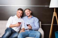Love and relationships. Two guys together on couch royalty free stock photos