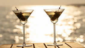 Two martini cocktails at the wooden pier at sunset. Luxury resort vacation concept. Festive relax getaway background. royalty free stock images