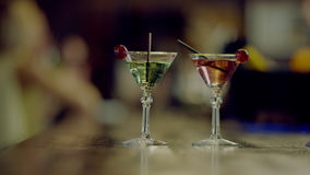 Two martini glasses on a bar counter. Close up view of two martini glasses standing on a bar counter with bartender cleaning a bar counter on background stock video