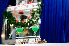 Two martini glasses with Christmas green cocktail on blue backgr. Ound Stock Images