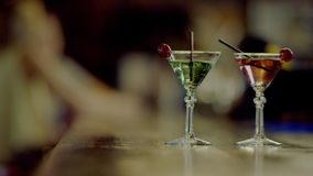 Two martini glasses. Close up view of two martini glasses standing on a bar counter stock footage
