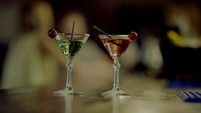 Two martini glasses. Close up view of two martini glasses standing on a bar counter with bartender cleaning a bar counter on background stock video footage