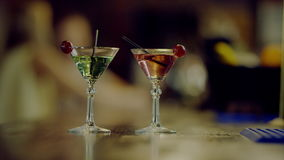 Two martini glasses. Close up view of two martini glasses standing on a bar counter, bartender gives cocktails in high glasses to two pretty girls stock video footage