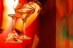 Martini glasses hanging with red background. Two martini glasses hanging with a strong red color background Stock Photos