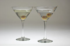 Two martini glasses with olives. Photographed against a white background and lit from underneath Stock Photo
