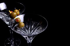 Two martini glasses with olives on black Stock Images