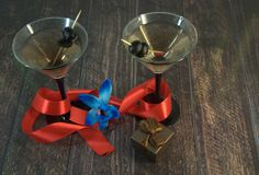 Two martini glasses with olives, with scarlet ribbon, blue orchid and gift box on a wooden table stock photo