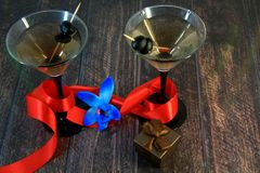 Two martini glasses with olives, with scarlet ribbon, blue orchid and gift box on a wooden table stock photos