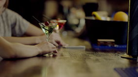 Two martini glasses with women's hands beside. Close up view of martini glasses with a cocktail standing on a bar counter with woman's hand beside, two young stock footage