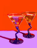 Two Martinis on Red. Two martini glasses vectored from a photo under neon lights Royalty Free Stock Images
