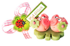 Two marzipan pigs with cloverleaf and good luck (in German) written on a background. Isolated Stock Images