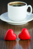 Two marzipan red candy and cup of black coffee Stock Photo