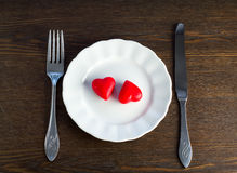 Two marzipan red hearts on a plate Royalty Free Stock Photos