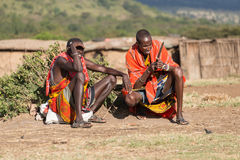 Two Masai men sitting in village compound. Two Masai men in traditional tribal dress sit in the middle of the village compound. One is shading his eyes against Stock Photography