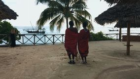 Two Masai people dances national dance at sunset and bids farewell to the sun.4K. Two Masai people dances their national African dance on the Indian Ocean beach stock video footage