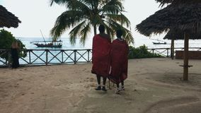 Two Masai people dances national dance at sunset and bids farewell to the sun.SM. Two Masai people dances their national African dance on the Indian Ocean beach stock footage