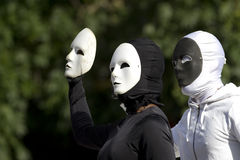 Two masked actors wearing black and white suits. Stock Photography