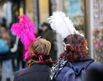 Two masked women with big feathers around Venice Italy Royalty Free Stock Photo