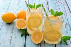 Two mason jar glasses of lemonade on rustic blue wood. Two mason jar glasses of homemade lemonade on a rustic blue wood background Stock Photography