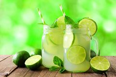 Two mason jars of limeade against a green outdoors background Stock Image