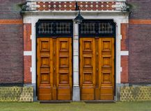 Two massive wooden doors with a lantern, Modern architecture, entrance door. Two massive wooden doors with a lantern, Modern architecture, a entrance door royalty free stock photo