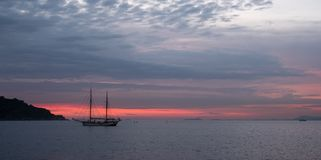 Two mast sailing boat in the far distance on the horizon off the coast of Italy in the Bay of Naples near Sorrento in Italy. Two mast sailing boat in the far royalty free stock photography