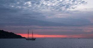 Two mast sailing boat in the far distance on the horizon off the coast of Italy in the Bay of Naples near Sorrento in Italy. Two mast sailing boat in the far stock photography