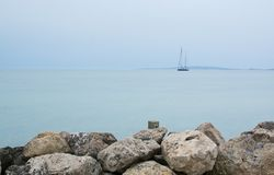 Two-masted sailing yacht. Near horizon and rocks on an overcast day in Molinar, Mallorca, Spain Stock Photography